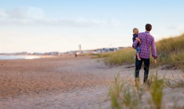 Father and daughter walking on the beach after following a family finance plan