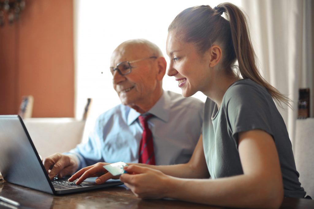 young woman helping grandfather make payment online