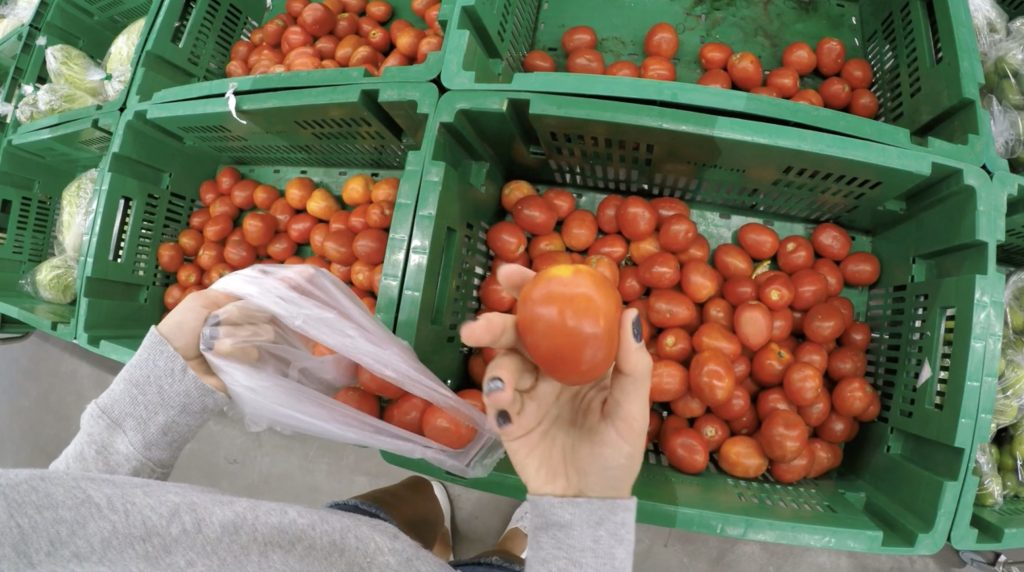 grocery shopping holding tomato