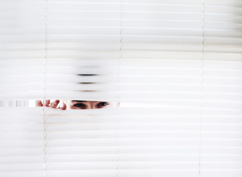 person peaking through blinds