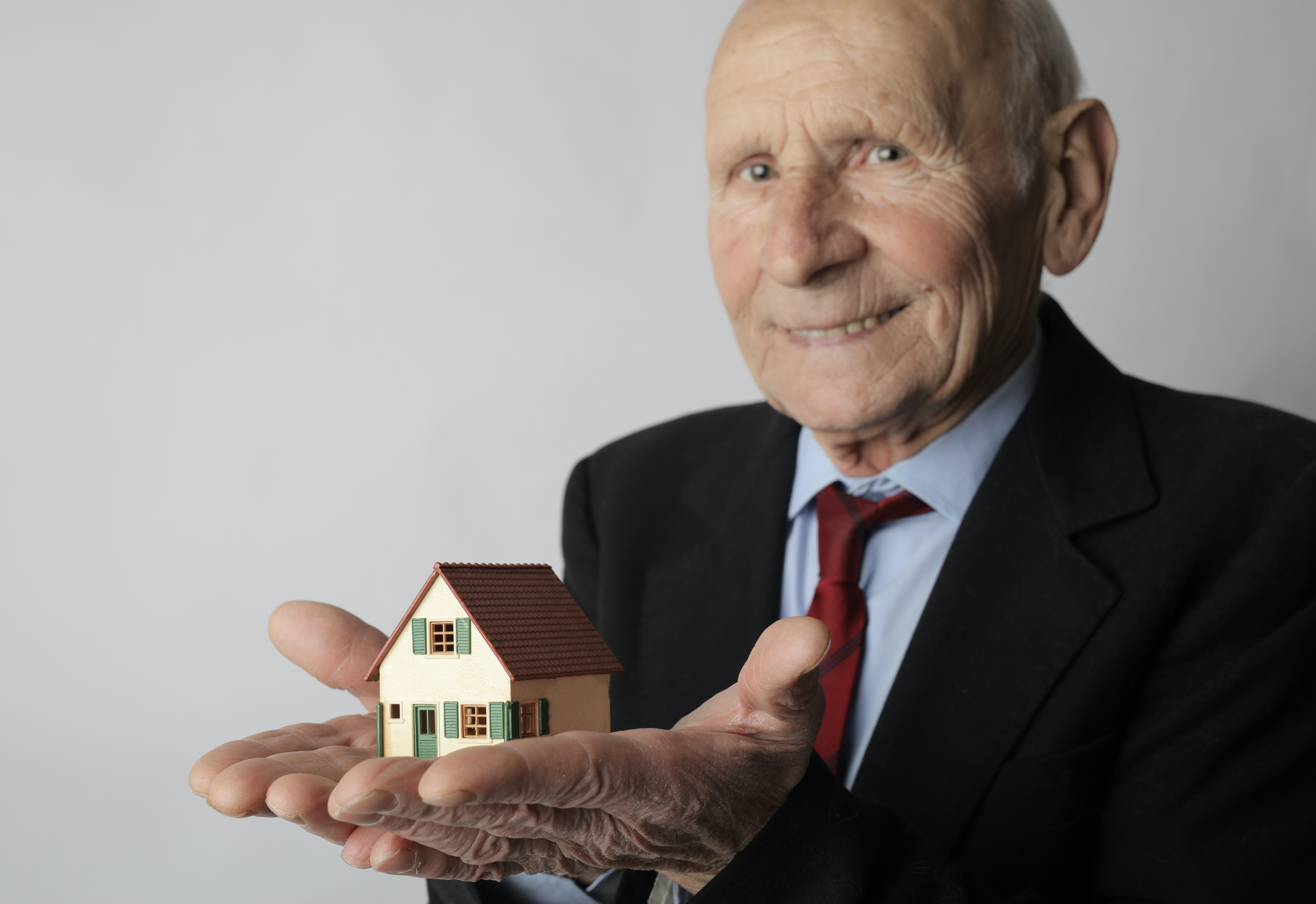 Old man holding model house